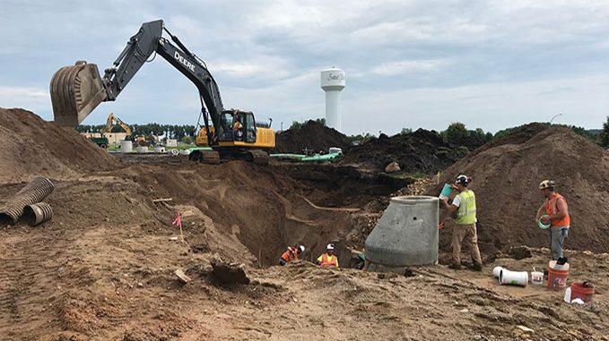 Crews work 12 feet under ground to place concrete pipe.