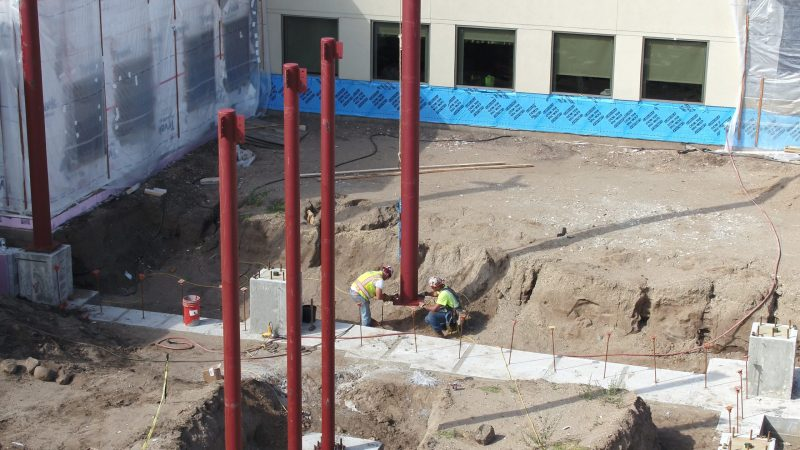 Construction crews placing a beam that will help stabilize the foundation of the emergency department wing.