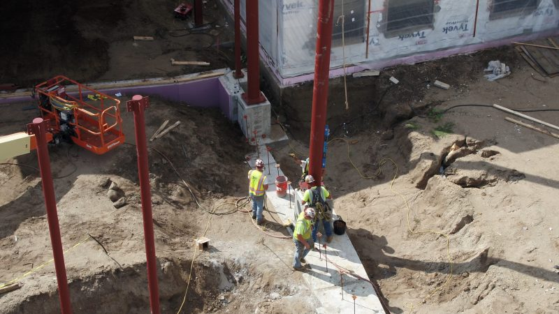 Construction crews work to install helical piles