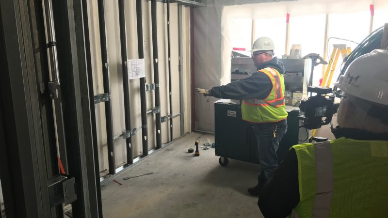 Rick Valli explains where the head wall in one of the new River's Edge patient rooms will be installed.
